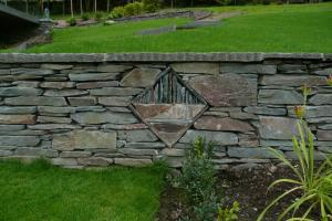 A sculpture built within a stone wall using local elterwater slate