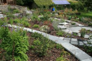 The garden is terraced with traditional stone walls capped with slate slabs that